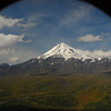 Giant snow-capped Ilchinski volcano framed in the porthole of the helicopter