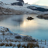 The Old Man of Storr standing high over a frozen lake