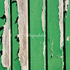 Peeling green plate on a wooden gate