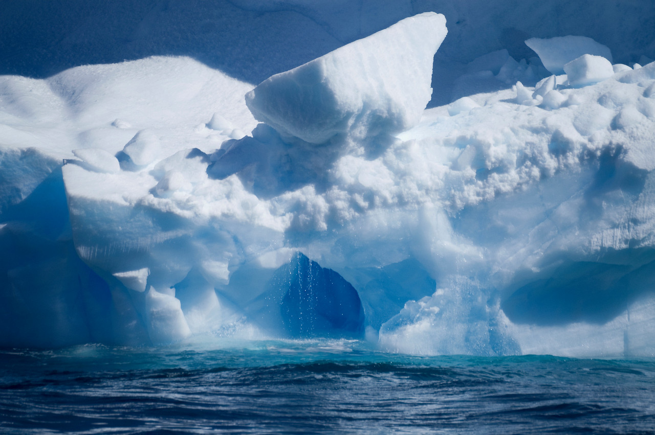 Iceberg with melt water pouring into the sea. January is summer in Antarctica.