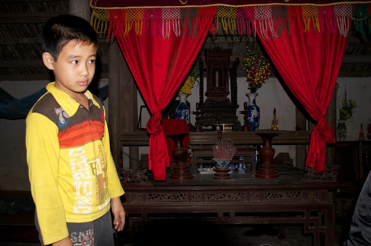 Boy by Buddhist Altar