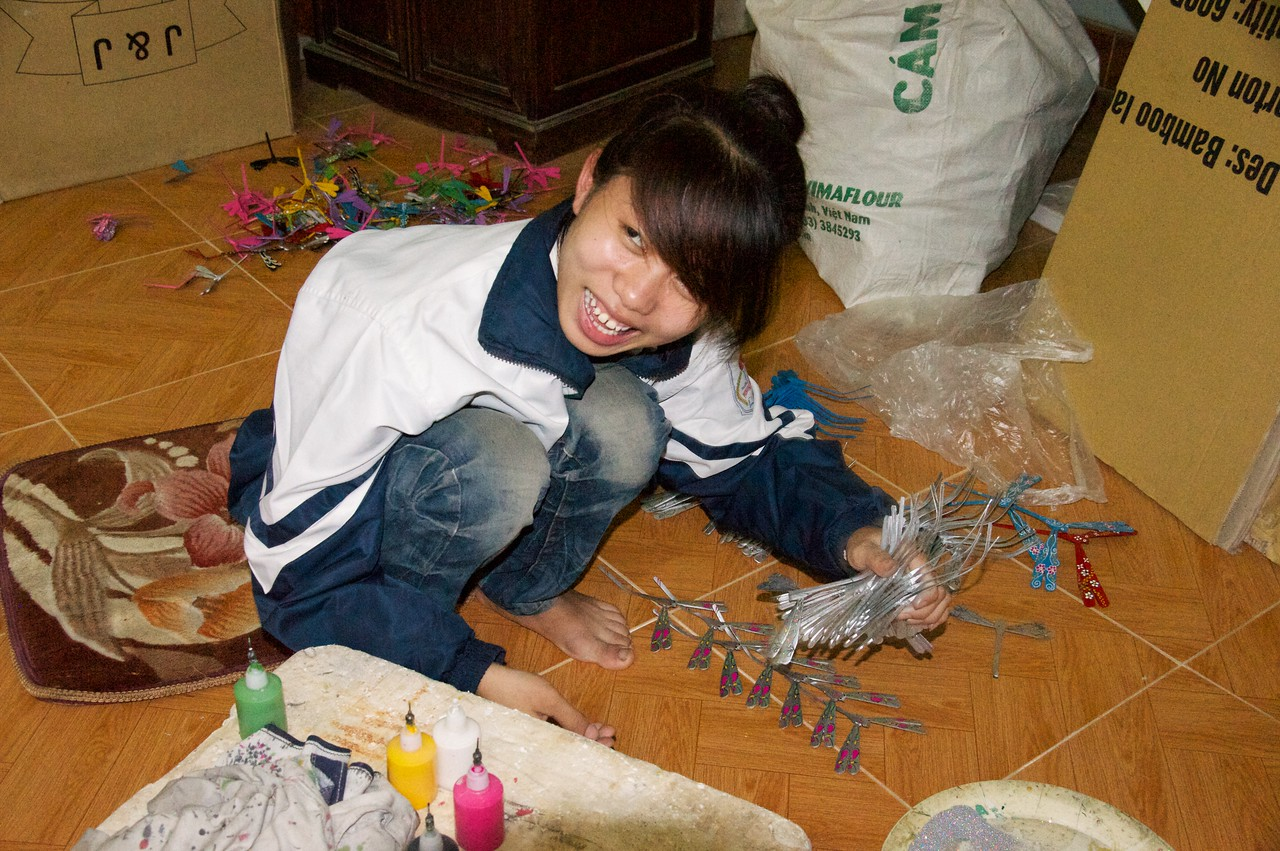 High school student painting dragon fly models as an after school job.