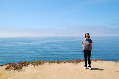 Lisa standing on a cliff about 300 feet above the Pacific ocean, with fog in the background - one of our stops along the Pacific Coast Highway.