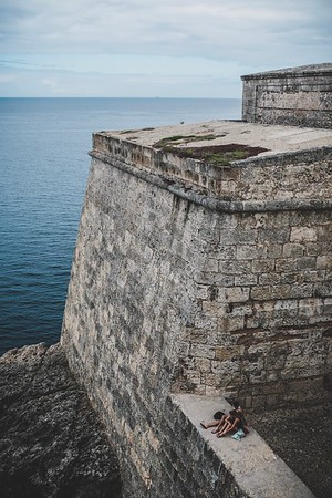 A young couple enjoys the water view of Castillo de los Tres Reyes Magos del Morro