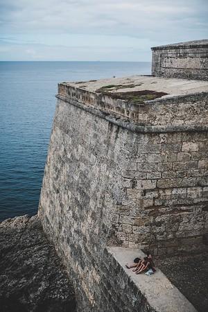A young couple enjoys the water view of Castillo de los Tres Reyes Magos del Morro