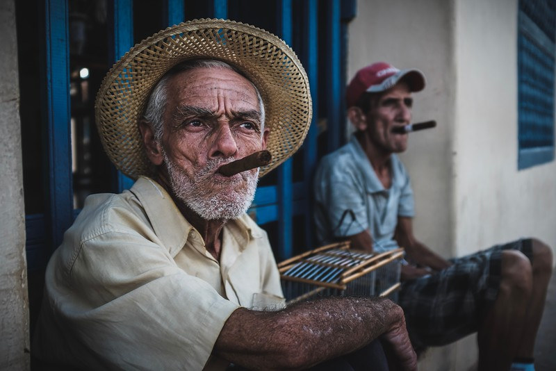 Two Cubans sit in a touristy area of Trinidad, accepting photo requests from passersby (for a fee).