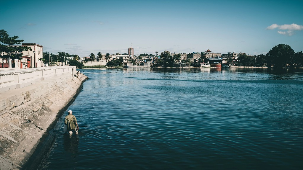 A man picks floating plastic bottles out of the water in Cienfuegos, Cuba.