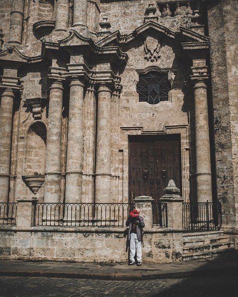A Cuban adjusts his red hat in front of the Havana Cathedral