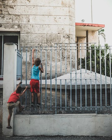 Kids play on the fence of a building in Havana, Cuba.