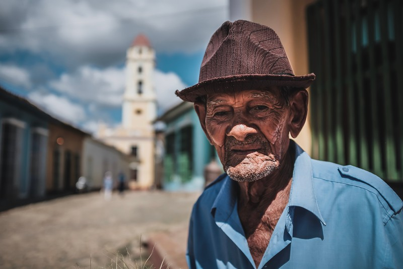 A deaf man stands in the sun in Trinidad, Cuba, selling trinkets made of grass blades.