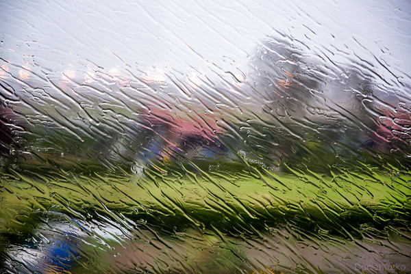 French countryside through a rain-soaked bus window.