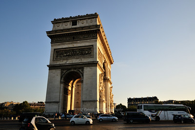 Arc de Triomphe from the side, with many little cars racing around it in one of the biggest roundabouts in Paris.
