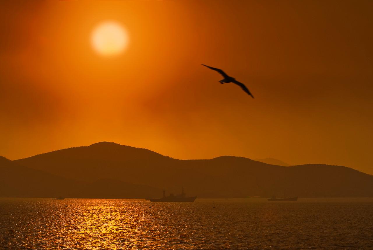Athens<br /> sun shrouded by smoke Pereus harbor Athens