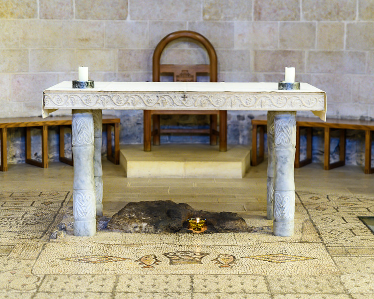 Closeup of the altar over the venerated rock where Jesus sat the bread as he broke it while feeding the multitude.  In front of it is the mosaic of the loaves and fishes; notice that there are only four loaves shown as the fifth was often in the hands of the priest or on the altar directly.