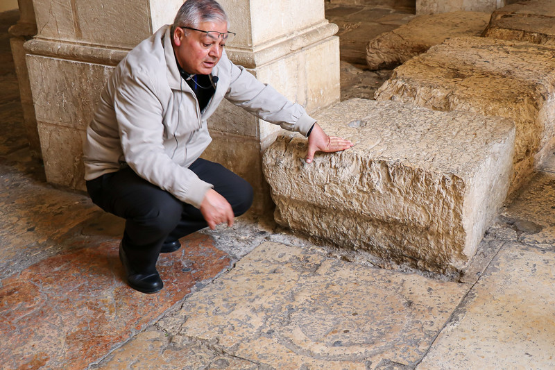 Hani shows how the soldiers may have cast lots (John 19:24) for Jesus clothing in a game of chance with coins and a circle carved and still visible in a paving stone.