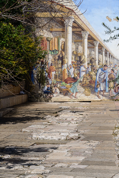 Mural of Roman days positioned at the end of a roadway that retains some of its ancient pavement stones