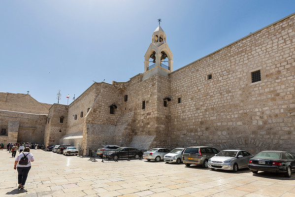 The Church of the Nativity, also Basilica of the Nativity is a basilica located in Bethlehem in the Palestinian West Bank.  The Armenian monastery (right) and facade of the Church of the Nativity (left, small).  The grotto it contains holds a prominent religious significance to Christians of various denominations as the birthplace of Jesus.  The original basilica was completed sometime between 333 and 339. It was destroyed by fire during the Samaritan revolts of the sixth century, and a new basilica was built in 565 by Byzantine Emperor Justinian, who restored the architectural tone of the original. The Church of the Nativity, while remaining basically unchanged since the Justinian reconstruction, has seen numerous repairs and additions, especially from the Crusader period, such as two bell towers (now gone), wall mosaics and paintings (partially preserved). Over the centuries, the surrounding compound has been expanded, and today it covers approximately 12,000 square meters, comprising three different monasteries: one Greek Orthodox, one Armenian Apostolic, and one Roman Catholic, of which the first two contain bell towers built during the modern era.