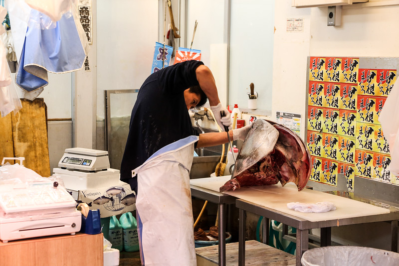 A fishmonger slicing up the head of his prized possesion from the morning auction