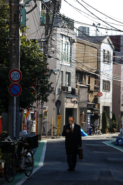 Japanese Business man keeping his eyes to his mobile.
