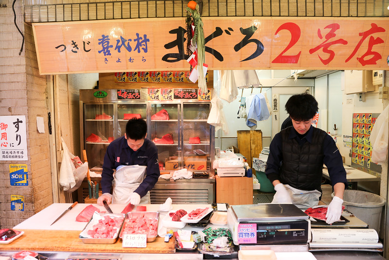 Preparing their auctioned fishes , slicing it using their marked Japanese knife