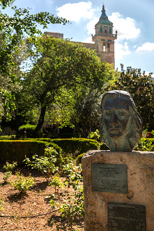 A sculpture of Chopin with he Royal Carthusian Monastery  behind it