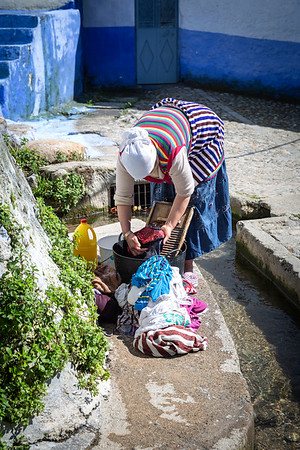 Woman washes clothes from a runoff from the nearby river