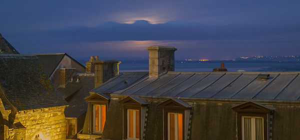 Moonrise over rooftops.