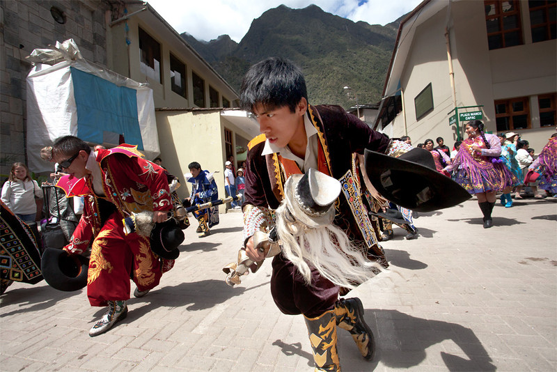 Young men celebrate in a costumed parade in downtown Aguas Calientes