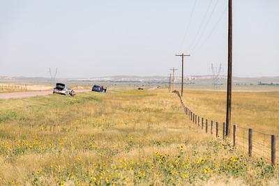 Cars lining up along the roadside.