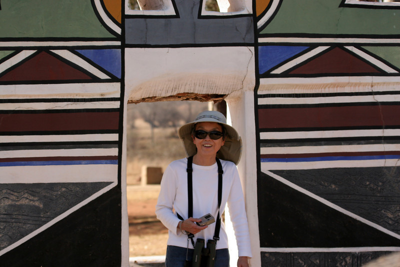 Karen exiting a Ndebele home. Very eye-catching hand painted wall design.