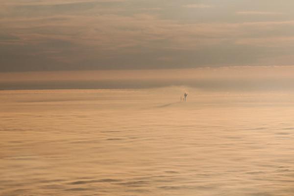 Sunrise near Toledo, Ohio. Only some factory's smokestacks penetrate the layer of fog.