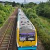 A train pulling into the Llanfairpwllgwyngyllgogerychwyrndrobwllllantysiliogogogoch, Wales, UK, train station as seen from a walkway over the tracks.
