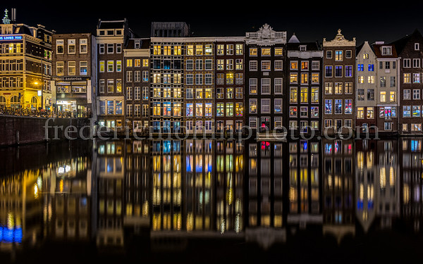 Houses along the Damrak channel at Amsterdam by night