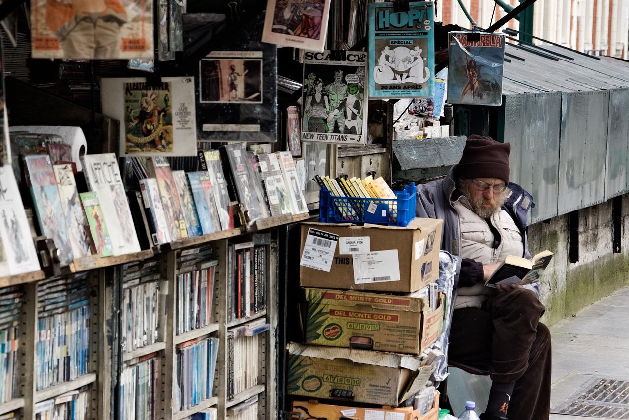 Book vendor in Paris enjoys his own wares.