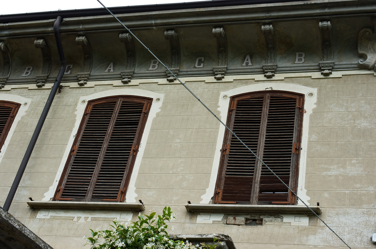 """Historic architecture of a school building in Serraluna d'Alba in the Piedmont wine region of Italy. Note the """"A, B, C's"""" under the roof."""
