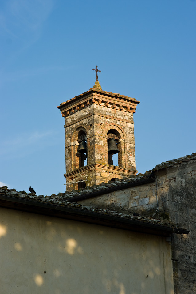 Tower, bell and cross on the roof tops of the Tuscany town of Strove, Italy.