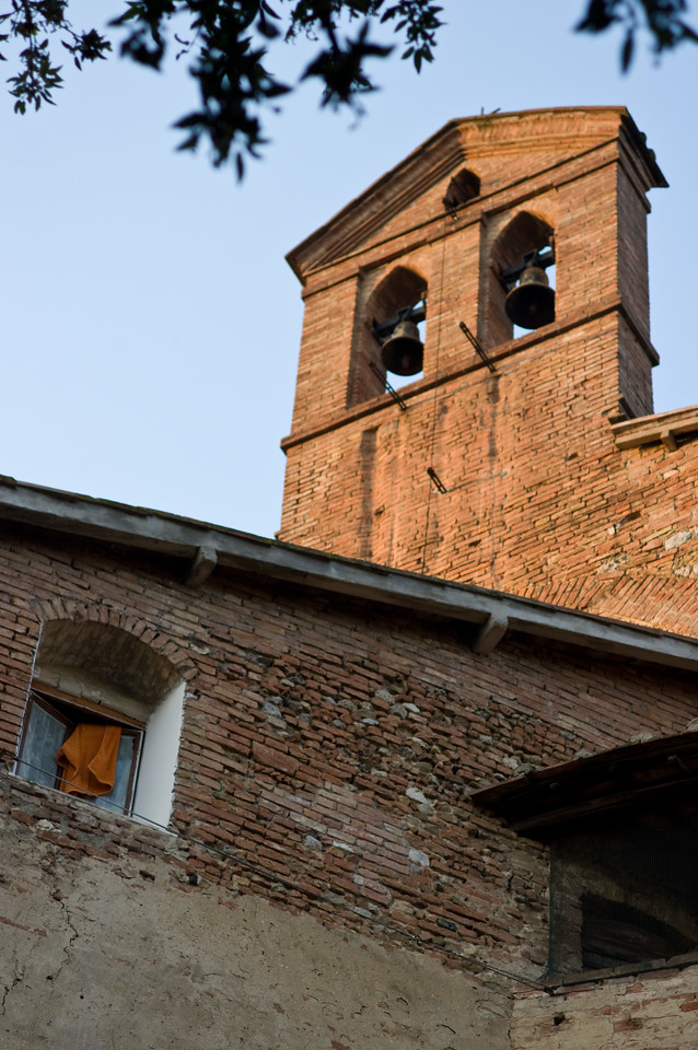 Bell tower and open window at sunset in Tuscany town of Strove, Italy.