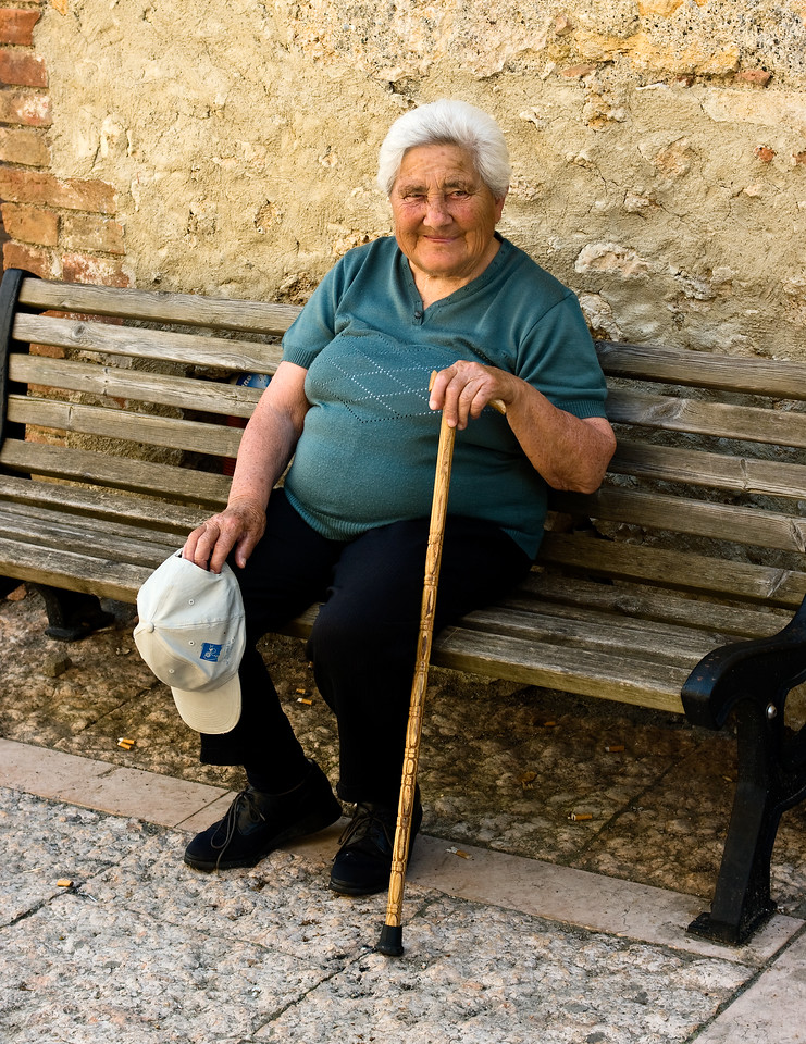 Old women relaxes on a bench in the Tuscan town of Strove, Italy.