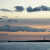 Twilight clouds above Cape Pembroke lighthouse as viewed from RRS James Clark Ross as she leaves Stanley bound for Mare Harbour, Falkland Islands