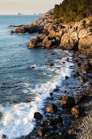 Waves on sunlit rocky shore, Dongbaek board walk, Busan, Korea