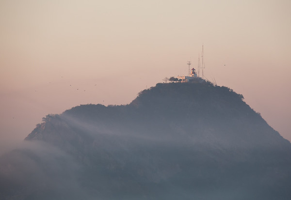 Dawn sun catches El Faro on a misty morning in Mazatlan