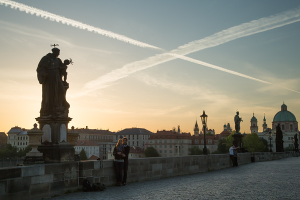 Couples pose for their sunrise selfies under the Statue of St. Anthony of Padua on Charles Bridge, Prague