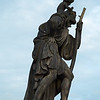 Statue of St. Christopher carrying a young Christ with transitory pigeon on Charles Bridge, Prague