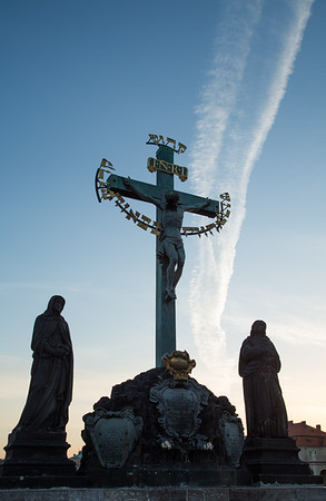 Early morning vapour trails over the statuary of the Holy Crucifix and Calvary, Charles Bridge, Prague
