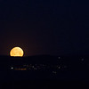 Full moon setting behind village lights