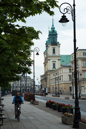 Cyclist, street lamps and towers of Holy Cross Church on Krakowskie Przedmiescie, Warsaw, Poland