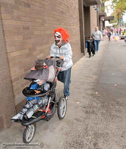 Dad Juaquin Melendez wears a scary clown mask as he pushes 3-year-old Jayden Melendez in a stroller during Treat Street in downtown Chico, Calif. Monday Oct. 31, 2016. (Bill Husa -- Enterprise-Record)