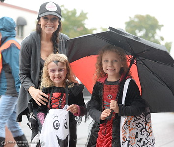 Left to right, Jayme Schlager smiles beside Hailey Schlager and Sage Nelson as they get candy during Treat Street in downtown Chico, Calif. Monday Oct. 31, 2016. (Bill Husa -- Enterprise-Record)