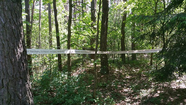 Strung out between the trees is a ribbon containing names of those who perished here.