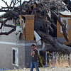 Travis Befus talks on the phone as he surveys damage after a giant cottonwood tree fell on the house where he lives with his wife and 10 week old baby at 4049 Crawford Ct. in west Loveland.  (Photo by Jenny Sparks/Loveland Reporter-Herald)